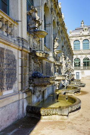 arched: DRESDEN, GERMANY - SEPTEMBER 19, 2015: Sculptures and fountains decorating the facade of the arched long gallery of Zwinger which was built in 1711-1728