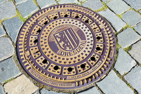 cobbles: DRESDEN, GERMANY - SEPTEMBER 19, 2015: Modern iron cover with the emblem of the city, made by the foundry company Eisenhamme, the sewer manhole located in the pavement made of cobbles