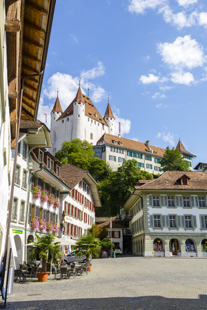 townhouses: THUN, SWITZERLAND - SEPTEMBER 08, 2015: The famous Thun Castle towering over the townhouses of the city. The castle was built in the 12th century, nowadays it houses the Thun Castle museum