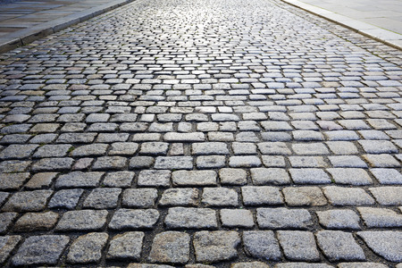 reflection: Cobbled stone road shown at a small angle, reflection of light seen on the road