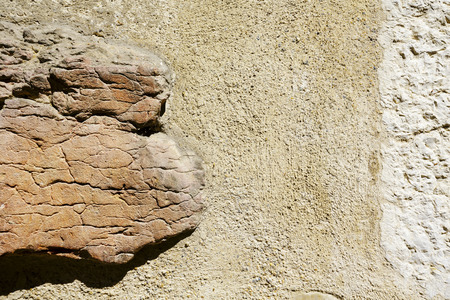 plastered: Old plastered wall with a visible protruding rock