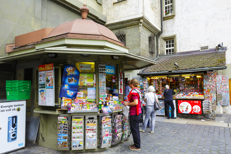 unrecognized: BERN, SWITZERLAND - SEPTEMBER 11, 2015: Unrecognized passerby do some shopping at a kiosk. Retail sales in heavily used areas provides daily access to many needed products and small gifts