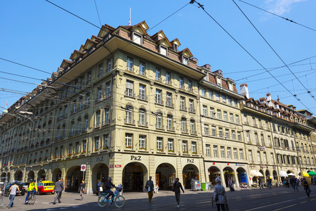 busy city: BERN, SWITZERLAND - SEPTEMBER 11, 2015: The Massive townhouse at Spitalgasse, and tram infrastructure creates an image of the busy city which is the fourth most populous city in the Country Editorial