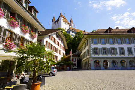 townhouses: THUN, SWITZERLAND - SEPTEMBER 08, 2015: The famous Thun Castle towering over the townhouses of the Town Hall Square. The castle was built in the 12th century, nowadays it houses the Thun Castle museum