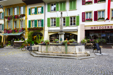 townhouses: MORAT, SWITZERLAND - SEPTEMBER 15, 2015: Townhouses and fountain at the most visited street in the old city of Morat Murten with a population of approx. 6,500 citizens. German and French linguistic region