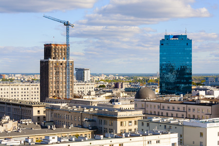 municipal editorial: WARSAW, POLAND - SEPTEMBER 30, 2015: Skyscrapers in the city, on left built in the years 1931-1933 as the seat of English Insurance Company, on the right it is a 22-storey office building Editorial
