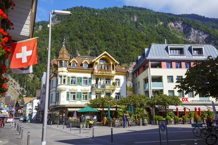 interlaken: INTERLAKEN, SWITZERLAND - SEPTEMBER 07, 2015: Alpine building with picturesque turret located in the heart of the city, on the ground floor housed famous Cafe de Paris, popular tourist destination
