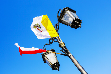 treaties: WARSAW, POLAND - OCTOBER 10, 2015: The Flag of Poland and the Flag of Vatican City in papal colors (yellow and white), officially adopted on June 7, 1929 under the Lateran treaties