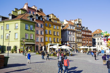 municipal editorial: WARSAW, POLAND - OCTOBER 10, 2015: Townhouses, Castle Square filled with tourists in the Old Town, destroyed up to the basement during World War II, rebuilt in the years 1949-1958