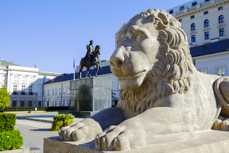 municipal editorial: WARSAW, POLAND - OCTOBER 10, 2015: Lion and Prince Jozef Poniatowski statue seen in the distance, by Danish sculptor Bertel Thorvaldsen, in front of the courtyard of the Presidential Palace Editorial