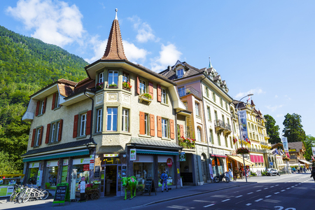 interlaken: INTERLAKEN, SWITZERLAND - SEPTEMBER 07, 2015: Picturesque townhouses in a very important tourist spot. The ground floor store Swiss Mountain Market offers Regional specialties and aromatherapy