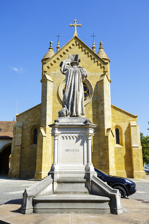 collegial: NEUCHATEL, SWITZERLAND - SEPTEMBER 09, 2015: The Collegiate Church it is a towering building on the castle hill, it was built in the 12th century, and the statue of the reformer William Farel