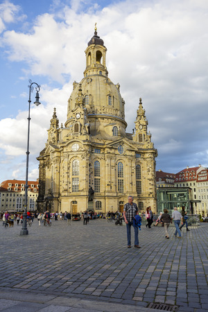 unrecognized: DRESDEN, GERMANY - SEPTEMBER 19, 2015: Unrecognized passerby walking on the New Market Square in front of Church of Our Lady. The Lutheran baroque church