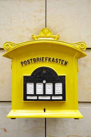 affixed: DRESDEN, GERMANY - SEPTEMBER 19, 2015: Painted yellow mailbox from the Federal Post Office is currently used by Deutsche Post AG Editorial