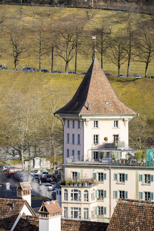 tenement buildings: BERN, SWITZERLAND - DECEMBER 22, 2015: House on the banks of the river in the 4th most populous city in the Country, it is visible from Nydeggbruecke Bridge which is a stone bridge over Aare river