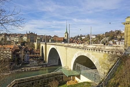 tenement buildings: BERN, SWITZERLAND - DECEMBER 22, 2015: Nydeggbruecke Bridge over River Aare. The bridge is made of stone, was built in 1844, the bridge is 190 meters long and 25 meters height Editorial