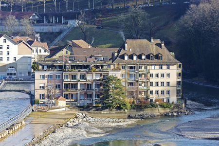 approx: BERN, SWITZERLAND - DECEMBER 22, 2015: Townhouses by the river. The river Aare flows through the city with a population of approx. 140000 citizens, it is the fourth most populous city in the country