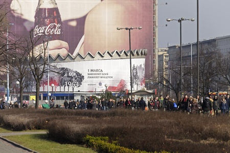 municipal editorial: Warsaw, Poland - February 28, 2016: A circular building with a slightly sloping roof shown in the background of the large area of advertising itself is wrapped in a big advertising poster. Editorial
