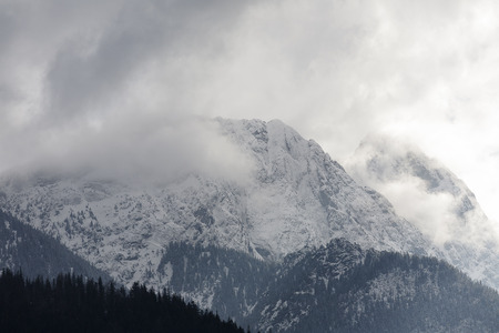giewont: Very well-known mountain called Giewont excels over the town of Zakopane. Giewont is shown in the midst of surrounding it clouds Stock Photo