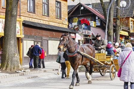 coachman: ZAKOPANE, POLAND - MARCH 06, 2016: Coachman is carrying tourists along Krupowki street in main shopping area and pedestrian promenade in the city center of Zakopane
