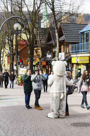 eagerly: ZAKOPANE, POLAND - MARCH 09, 2016: Unrecognized man portrays the role of a teddy bear, tourists eagerly wants to have photos with him. It is an attraction on the famous street Krupowki Editorial