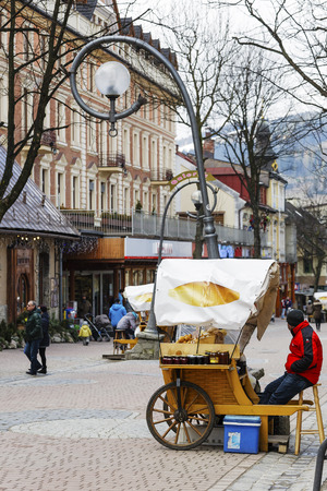culinary tourism: ZAKOPANE, POLAND - MARCH 09, 2016: Sales of Oscypek cheeses and other regional food products at Krupowki street, oscypek is Polish regional product protected by EU law since February 02, 2007