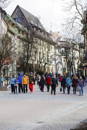 passerby: ZAKOPANE, POLAND - MARCH 09, 2016: Unidentified people walk along Krupowki Street. It is main shopping area and pedestrian promenade in the downtown is very famous and frequently visited by tourists Editorial