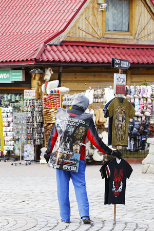 unrecognized: ZAKOPANE, POLAND - MARCH 09, 2016: Unrecognized man wears advertising banner in addition in hand holds the stick on which they are placed more promotional materials Editorial