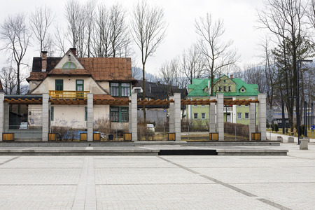 municipal editorial: ZAKOPANE, POLAND - MARCH 07, 2016: View over the Independence Square towards old residential house built about 1910 on the left and building of the former Municipal Baths built in 1928 on right side