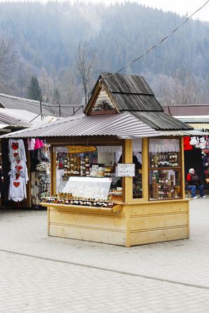 oscypek: ZAKOPANE, POLAND - MARCH 11, 2016: Selling regional food products at the stall situated at the largest marketplace in the city.