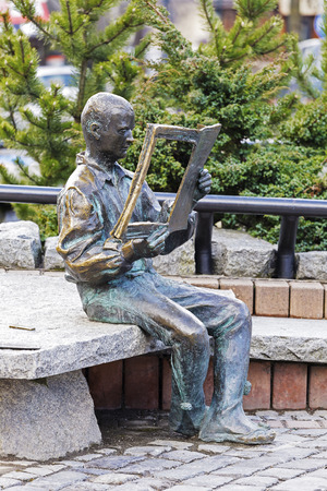 highlander: ZAKOPANE, POLAND - MARCH 09, 2016: Highlander sitting on a rock and reading a newspaper, made of bronze figure created to commemorate the 20th anniversary of the magazine Tygodnik Podhalanski