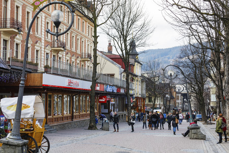 str: ZAKOPANE, POLAND - MARCH 09, 2016: Unknown passers are walking along Krupowki Str. It is main shopping area and pedestrian promenade in the downtown is very famous and frequently visited by tourists Editorial