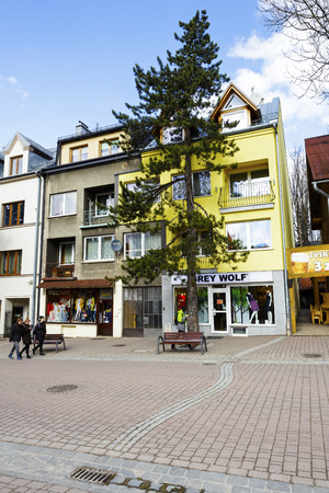 tenement buildings: ZAKOPANE, POLAND - MARCH 09, 2016: Brick townhouse probably from the early twentieth century, located at the lower part of  Krupowki. On the ground floor of this building there are two shops Editorial