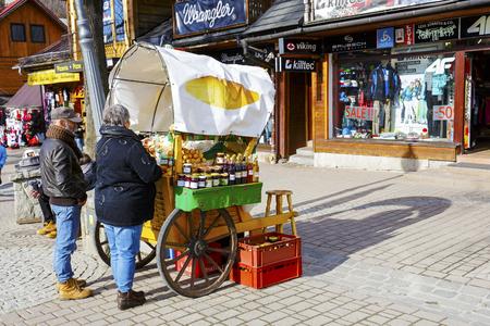 oscypek: ZAKOPANE, POLAND - MARCH 06, 2016: Unidentified couple are buying Oscypek cheese at Krupowki street, since February 02, 2007 Oscypek is Polish regional product protected by EU law
