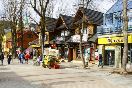 passerby: ZAKOPANE, POLAND - MARCH 06, 2016: General view at Krupowki street. It is main shopping area and pedestrian promenade in the downtown is very famous and frequently visited by tourists Editorial