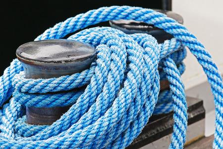 bollard: The mooring bollard and a blue rope fixed on it. Stock Photo