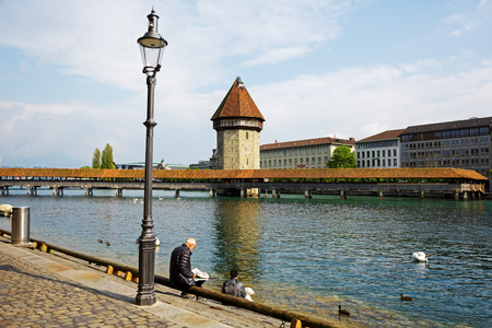 unrecognized: LUCERNE, SWITZERLAND - MAY 02, 2016: Unrecognized people are sitting on the banks of the river Reuss. They can see a views of the Chapel Bridge (Kapellbruecke) with its tall tower (Wasserturm)