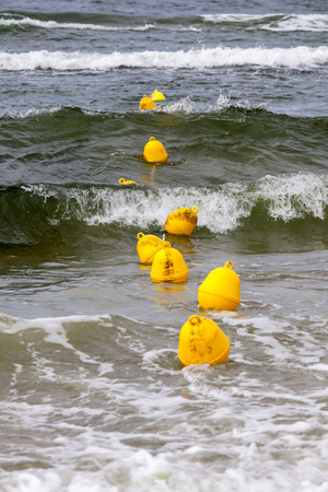 buoys: Yellow buoys on the surface of the sea of Baltic define the boundary of the safe swimming at the beach in Kolobrzeg in Poland Stock Photo