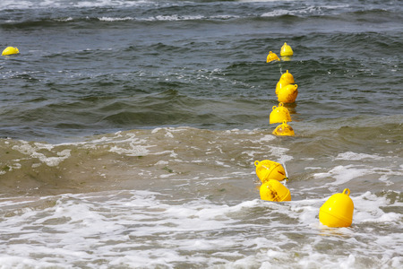 define: Yellow buoys on the Baltic sea waters define the boundary of the safe swimming at the beach in Kolobrzeg in Poland