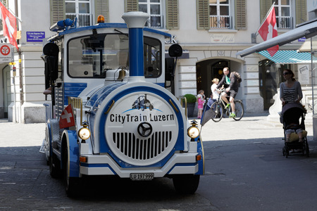 trackless: LUCERNE, SWITZERLAND - MAY 08, 2016: Blue and White Trackless Train travels through the streets of the city providing a convenient way for tourists to see variety of sightseeing attractions Editorial