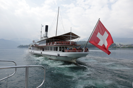 paddle wheel: LUCERNE, SWITZERLAND - MAY 03, 2016: Uri vessel departs from Ferry Terminal Verkehrshaus-Lido. It is  the oldest operating Swiss paddle wheel steamer and was built in 1901