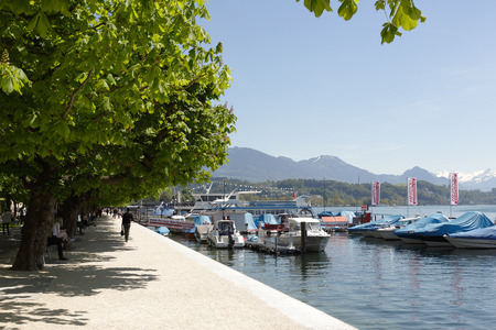 passerby: LUCERNE, SWITZERLAND - MAY 06, 2016: Promenade along the shore of Lake Lucerne is a walking place frequently visited by many tourists because of the magnificent views that can be seen from here Editorial