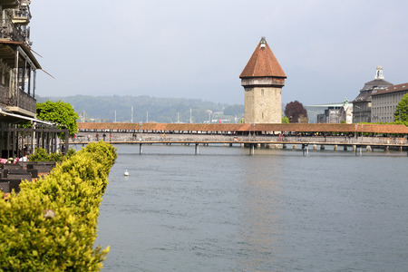 Lucerne, Switzerland - May 02, 2016: View towards the Chapel Bridge (Kapellbruecke) which joins two banks of the river Reuss together with the octagonal tall tower (Wasserturm) it is one of the Lucernes most famous tourists attraction. A few people can b