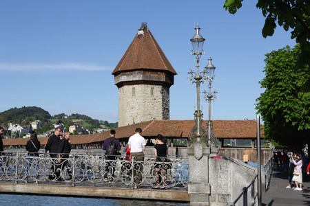 unidentified: LUCERNE, SWITZERLAND - MAY 09, 2016: Unidentified tourists are going on the pedestrians bridge and they watch roofed Chapel Bridge and The octagonal tall tower