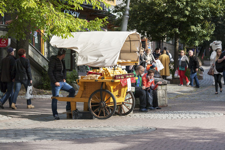 oscypek: ZAKOPANE, POLAND - SEPTEMBER 23, 2016: The booth that offers Oscypek cheese was placed at the street Krupowki. Oscypek is Polish regional product since February 2007 and it is protected by EU law