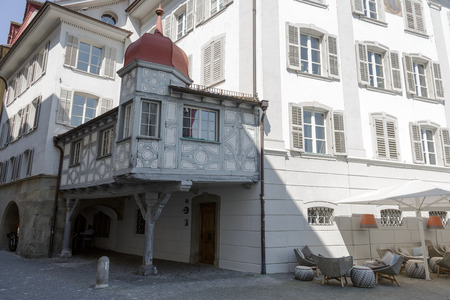 outbuilding: LUCERNE, SWITZERLAND - MAY 08, 2016: Made of wood outbuilding in a shaded backstreet of the old town contrasts with the furniture nearby cafe Editorial