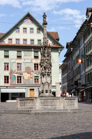 townhouses: LUCERNE, SWITZERLAND - MAY 10, 2016: Weinmarkt Fountain that is 15th-century fountain and is surrounded by historical buildings decorated with frescos and it is located at the square in the old town