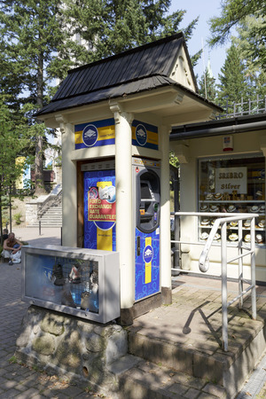 ZAKOPANE, POLAND - SEPTEMBER 13, 2016: ATM machine was placed on the street and was enclosed at the small construction which relates to the architectural style of the region