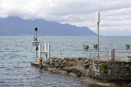 Breakwater equipped with warning devices on Lake Geneva in Montreux. On the other side of the lake forested hills can be seen in the distance.