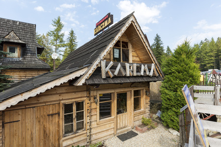 defines: ZAKOPANE, POLAND - SEPTEMBER 12, 2016: Wooden building architecture is reminiscent of the style of the region. Large lettering defines the use of the building, this is regional restaurant Editorial
